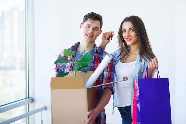 Jong volwassen paar binnen zaal met dozen die de banner van nieuw huissleutels houden. Premium Foto