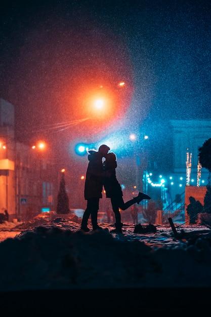 Jong volwassen paar in elkaars armen op besneeuwde straat Gratis Foto