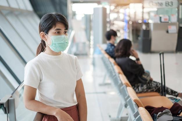 Jong volwassen wijfje dat gezichtsmasker in luchthaventerminal draagt Premium Foto