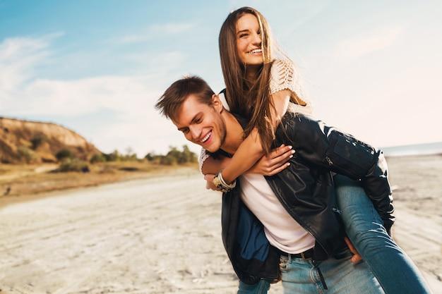 Jong volwassenen vriendin en vriendje gelukkig knuffelen. jong mooi paar in liefde die op de zonnige lente langs strand dateren. warme kleuren. Gratis Foto