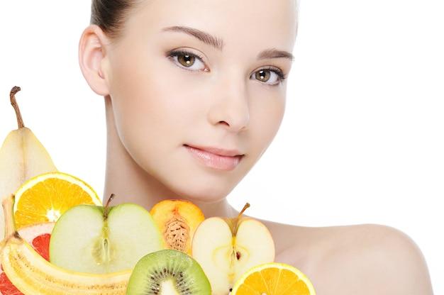 Jong vrouwelijk gezicht met vers fruit dat op wit wordt geïsoleerd Gratis Foto