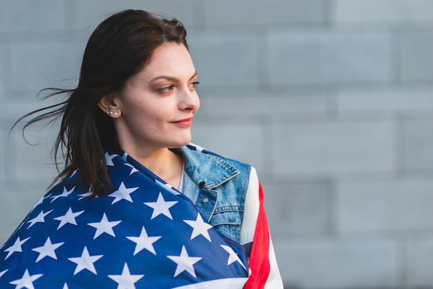 Jong wijfje dat in amerikaanse vlag oprolt Gratis Foto