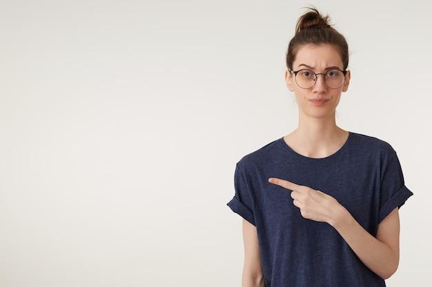 Jong wijfje in glazen in t-shirt die met irritatie opzij wijzen, die zich over witte muur bevinden Gratis Foto
