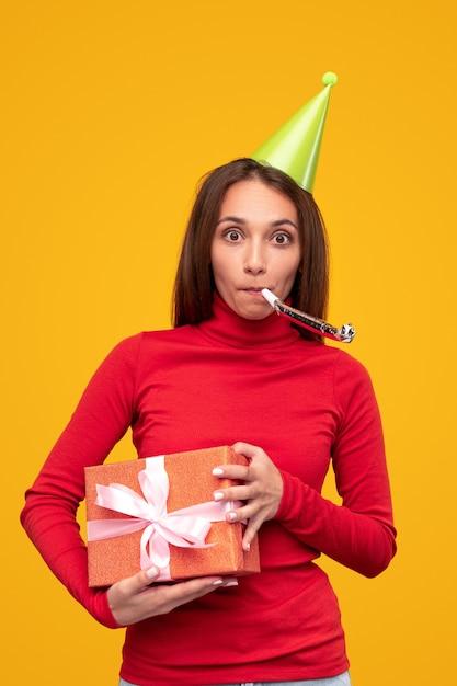 Jong wijfje in rode coltrui en partij glb die giftdoos draagt en noisemaker blaast tijdens verjaardagsviering tegen gele achtergrond Premium Foto