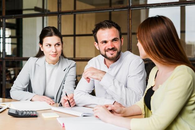 Jong zakenlui die hun project in bureau bespreken Gratis Foto