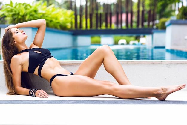 Jong zonnen fitnessmodel lag op de vloer, mode-luxe minimalistische stijl Gratis Foto