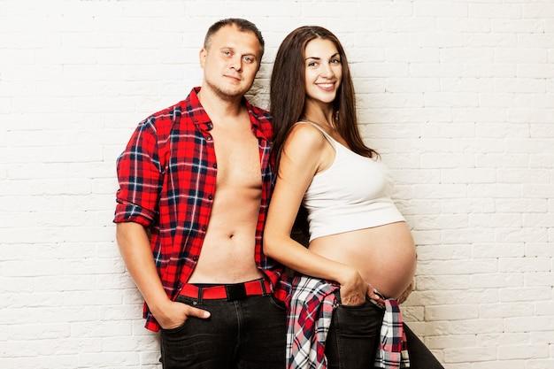 Jong zwanger en paar dat koestert glimlacht. wachten op geboorte en tedere relatie. Premium Foto