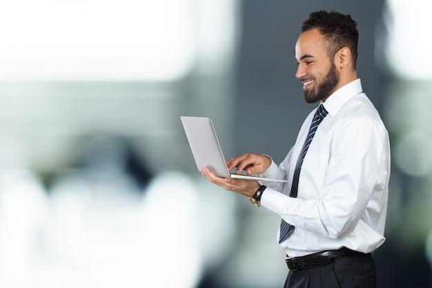 Jong zwart mannelijk holdingslaptop geïsoleerd portret Premium Foto