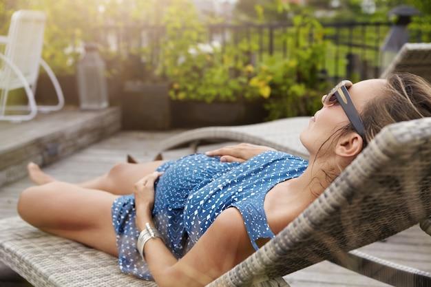 Jonge aanstaande moeder die een zonnebril en zomerjurk draagt die slaapt of een dutje doet op een ligstoel, de handen op haar buik houdt. Gratis Foto