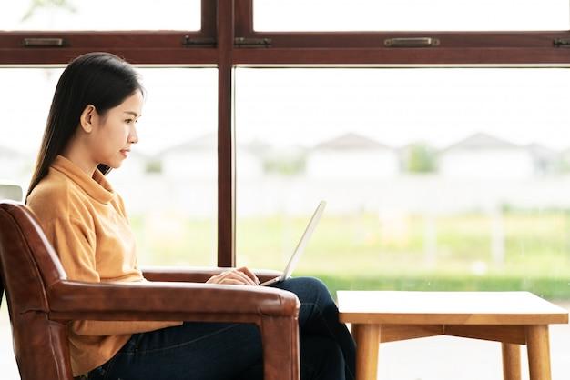 Jonge aantrekkelijke aziatische vrouw zitten of werken bij café Premium Foto