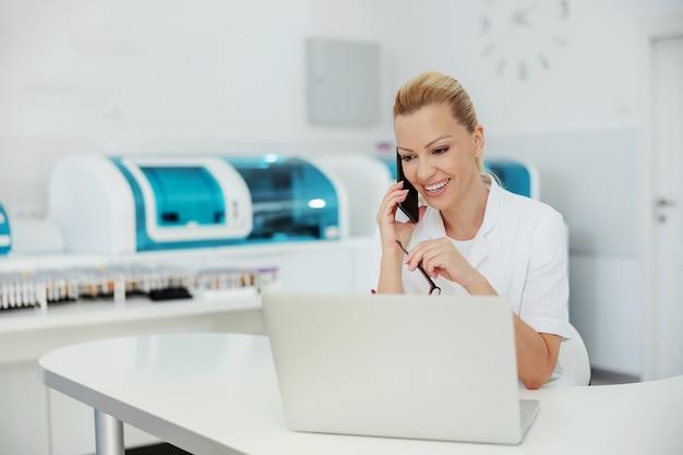 Jonge aantrekkelijke blonde laboratoriumassistent in het laboratorium zitten en praten aan de telefoon met de patiënt. Premium Foto