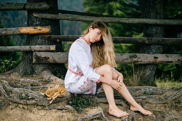 Jonge aantrekkelijke blonde meisje op blote voeten in witte jurk met ornament zitten in de buurt van houten hek buitenshuis Premium Foto