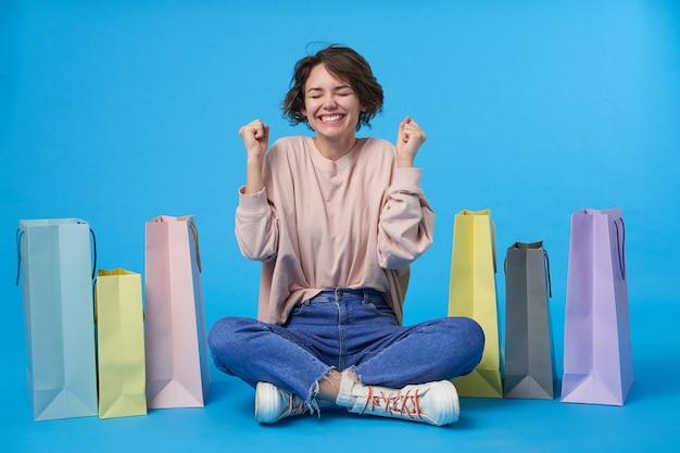 Jonge aantrekkelijke donkerharige vrouw met kort kapsel met veel boodschappentassen Gratis Foto