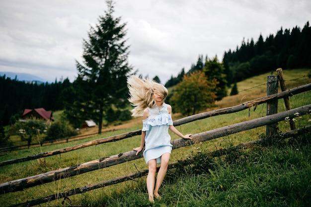 Jonge aantrekkelijke elegante blonde meisje in blauwe jurk met vliegend haar poseren in de buurt van hek op het platteland Premium Foto