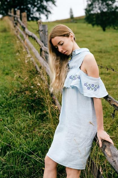 Jonge aantrekkelijke elegante blonde meisje in blauwe jurk poseren in de buurt van hek op het platteland Premium Foto