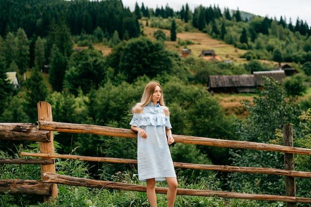 Jonge aantrekkelijke elegante blonde meisje in blauwe jurk poseren in de buurt van houten hek op het platteland Premium Foto