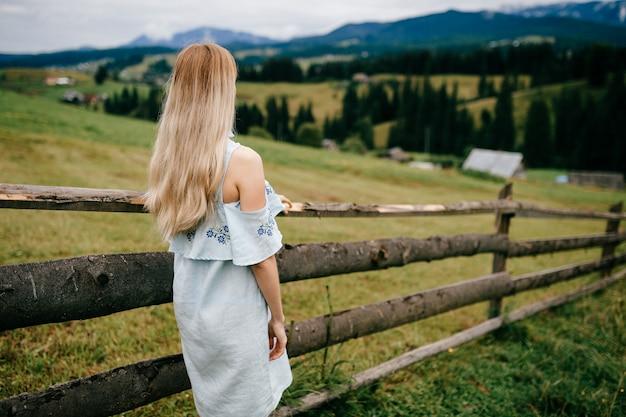 Jonge aantrekkelijke elegante blonde meisje in blauwe jurk poseren terug in de buurt van hek op het platteland Premium Foto
