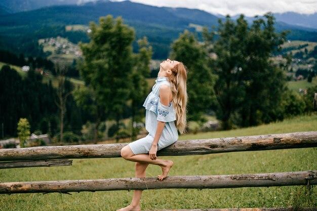 Jonge aantrekkelijke elegante blonde meisje in blauwe jurk zittend op het houten hek op het platteland Premium Foto