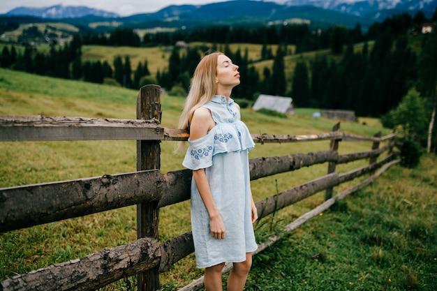Jonge aantrekkelijke elegante blonde meisje in blauwe romantische jurk poseren in de buurt van hek op het platteland Premium Foto