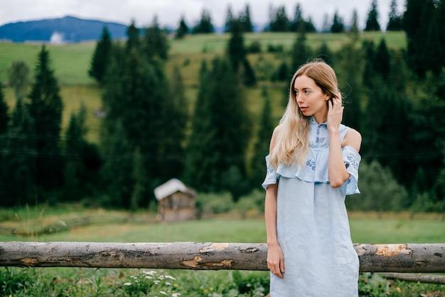 Jonge aantrekkelijke elegante blonde meisje in blauwe romantische jurk poseren in de buurt van houten hek op het platteland Premium Foto