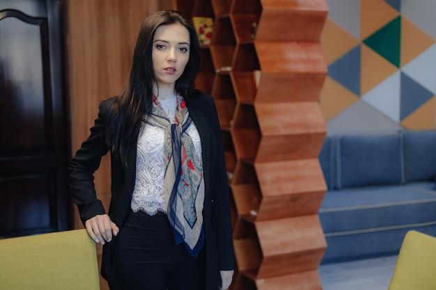Jonge aantrekkelijke emotionele meisje in een zakelijke stijl op een stoel in een modern kantoor of publiek Premium Foto