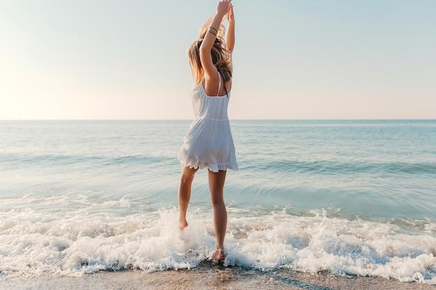 Jonge aantrekkelijke gelukkige vrouw dansen ronddraaien door zee strand zonnige zomer mode-stijl in witte jurk vakantie Gratis Foto