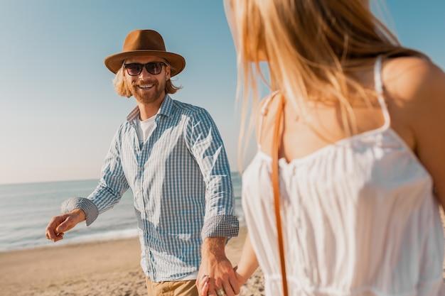 Jonge aantrekkelijke glimlachende gelukkig man in hoed en blonde vrouw in witte jurk die samen op strand loopt Gratis Foto