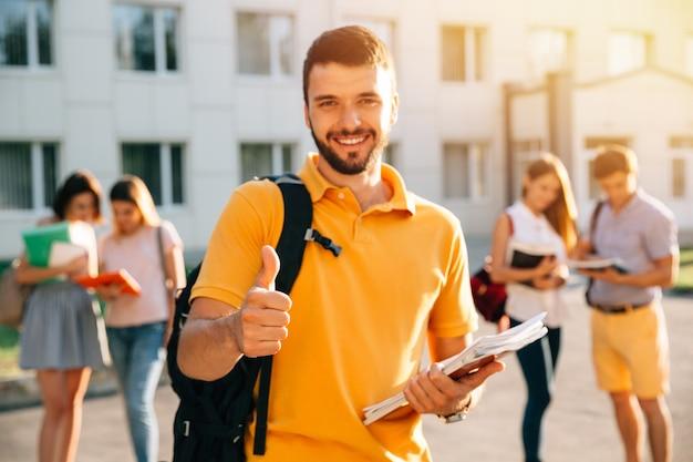 Jonge aantrekkelijke glimlachende student die duim in openlucht op campus toont bij de universiteit. Gratis Foto