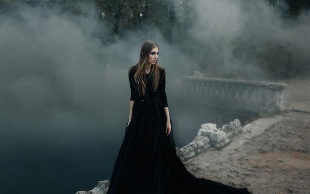 Jonge aantrekkelijke heks die op de brug in zware zwarte rook loopt. Premium Foto