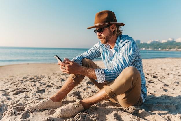 Jonge aantrekkelijke hipster man zittend op het strand aan zee op zomervakantie Gratis Foto
