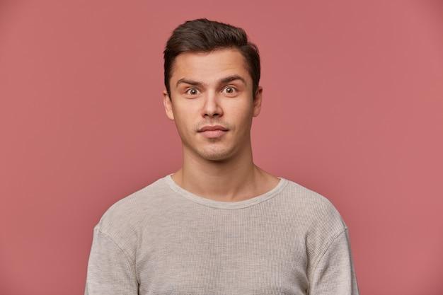 Jonge aantrekkelijke man in lege longsleeve, kijkt rustig naar de camera, staat op roze achtergrond. Gratis Foto
