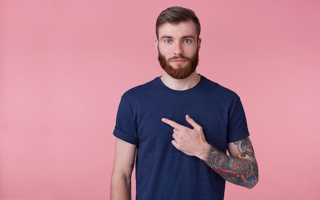 Jonge aantrekkelijke man met een rode baard, gekleed in een blauw t-shirt, kijkend naar de camera met een kalm gezicht. wijzende vinger in copys-tempo aan de linkerkant geïsoleerd over roze achtergrond. Gratis Foto