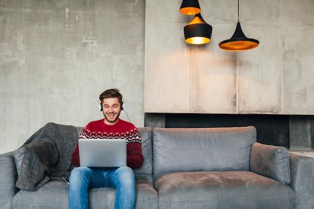 Jonge aantrekkelijke man op sofa thuis in de winter in koptelefoon, luisteren naar muziek, dragen rode gebreide trui, bezig met laptop, freelancer, glimlachen, gelukkig, positief Gratis Foto
