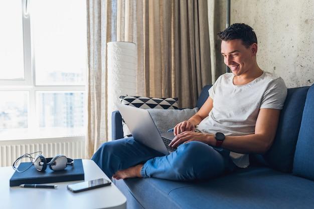 Jonge aantrekkelijke man zittend op de bank thuis werken op laptop online, via internet Gratis Foto
