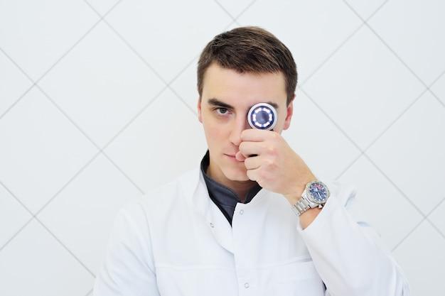 Jonge aantrekkelijke mannelijke artsendermatoloog met in hand dermatoscope Premium Foto