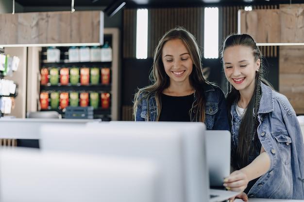Jonge aantrekkelijke meisjes in een elektronicawinkel gebruiken een laptop op een tentoonstelling Gratis Foto