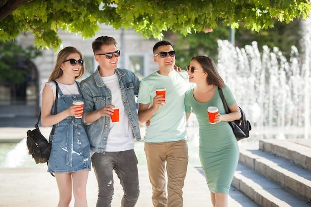 Jonge aantrekkelijke mensen plezier samen buitenshuis. mensen die koffie drinken en glimlachen. groep vrienden samen wandelen. Premium Foto
