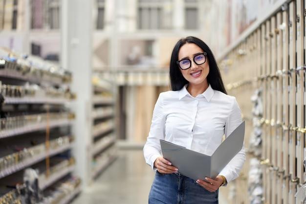 Jonge aantrekkelijke positieve meisjesverkoper op de achtergrond van het winkelcentrum Premium Foto