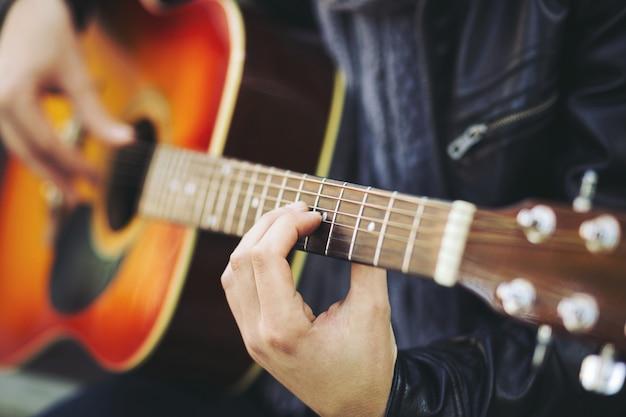 Jonge aantrekkelijke straatartiest met zijn gitaar Gratis Foto