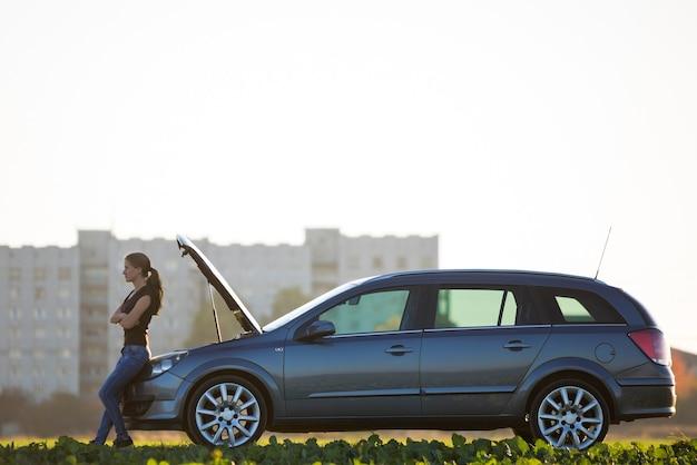 Jonge aantrekkelijke vrouw bij auto met open kap in groene weide op wazig flatgebouw Premium Foto