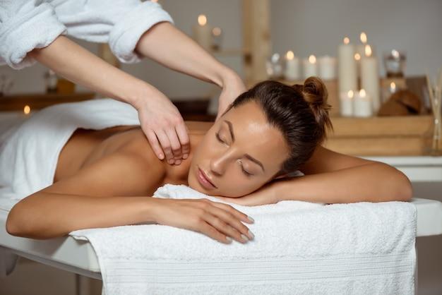 Jonge aantrekkelijke vrouw die massage het ontspannen in kuuroordsalon heeft. Gratis Foto