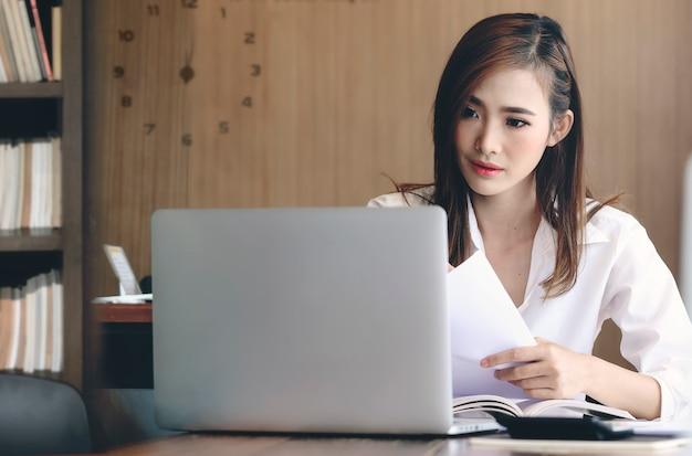 Jonge aantrekkelijke vrouw die met laptop werkt terwijl het zitten in uitstekend stijlbureau. Premium Foto