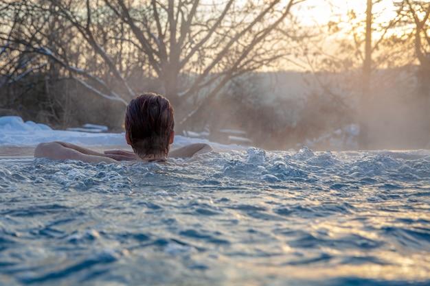 Jonge aantrekkelijke vrouw die van wellness met sauna en zwembad in openlucht in de winter geniet Premium Foto