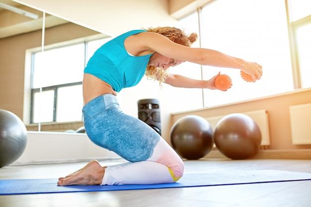 Jonge aantrekkelijke vrouw die yoga in fitnessruimte doet. Premium Foto