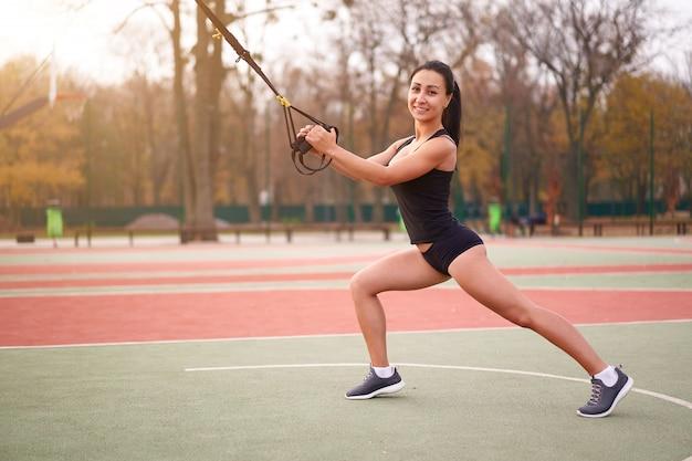 Jonge aantrekkelijke vrouw doet schorsing training met fitness bandjes buitenshuis Premium Foto