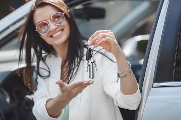 Jonge aantrekkelijke vrouw heeft net een nieuwe auto gekocht. vrouwelijke sleutels van nieuwe auto houden. Premium Foto