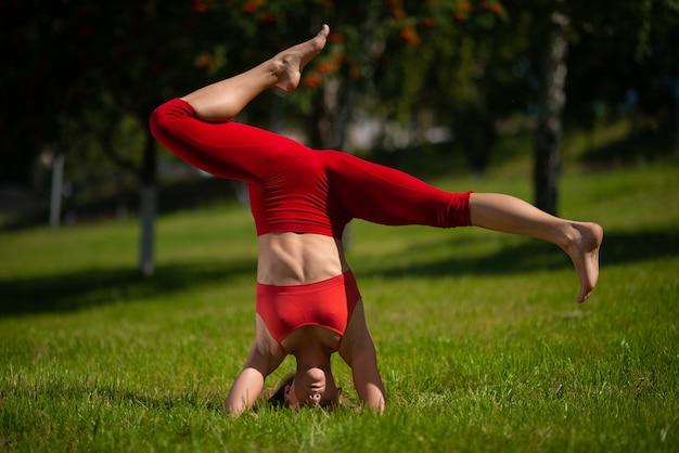 Jonge aantrekkelijke vrouw het beoefenen van yoga buitenshuis. het meisje voert een handstand ondersteboven uit Premium Foto