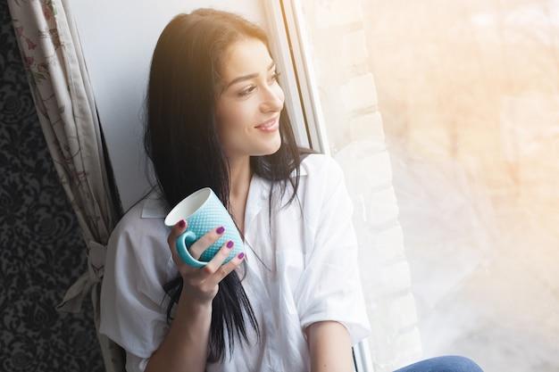 Jonge aantrekkelijke vrouw het drinken van thee of koffie in haar keuken. lady indors ontspannen met kop warme drank Premium Foto