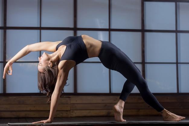 Jonge aantrekkelijke vrouw in bending side plank stelt, avond praktijk Gratis Foto