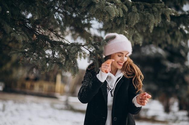 Jonge aantrekkelijke vrouw in een winter park in een schattige hoed Gratis Foto